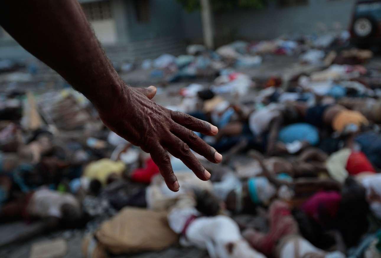 Το χέρι ενός άνδρα μπροστά από τα εκατοντάδες πτώματα που κείτονται έξω από το νεκροτομείο και το νοσοκομείο στο Πορτ-ο-Πρενς της Αϊτής. Η φωτογραφία τραβήχτηκε στις 15 Ιανουαρίου του 2010 ενώ η χώρα της Καραϊβικής προσπαθούσε να σταθεί ξανά στα πόδια της μετά τον φονικό σεισμό των επτά βαθμών της κλίμακας Ρίχτερ