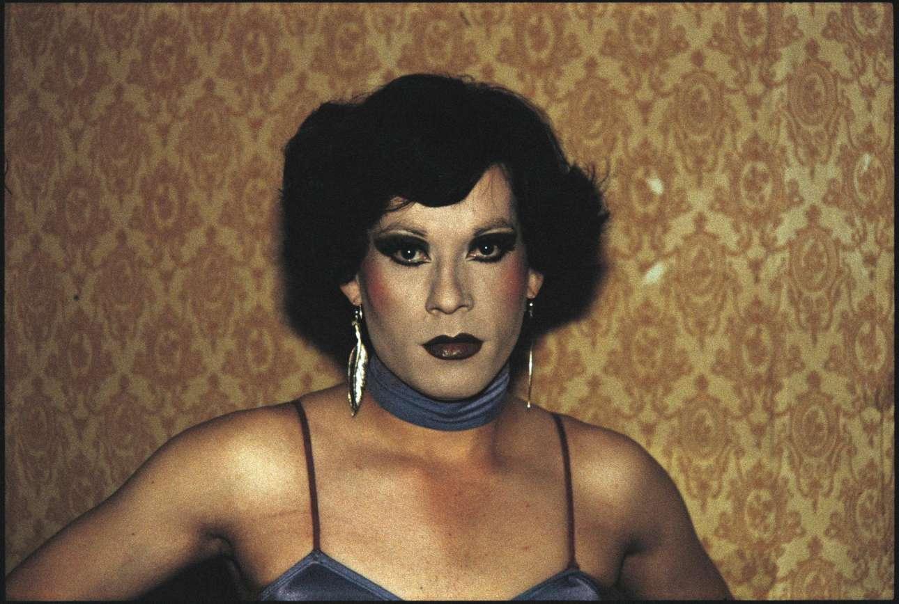 Paz Errázuriz, «Evelyn», Σαντιάγκο. Από τη σειρά Το Μήλο του Αδάμ (La Manzana de Adán), 1983. Το 1973, μετά το στρατιωτικό πραξικόπημα του Πινοσέτ στη Χιλή, η Παζ Εραζουρίζ παράτησε τη διδασκαλία και στράφηκε στη φωτογραφία «ως τον δικό της τρόπο να πάρει μέρος στην αντίσταση». Επέλεξε να απαθανατίσει ανθρώπους που βρίσκονταν στο στόχαστρο του νέου καθεστώτος, όπως οι τρανς που δούλευαν σε παράνομους οίκους ανοχής στις πόλεις Σαντιάγκο και Τάλκα, σαν την εικονιζόμενη Εβελυν