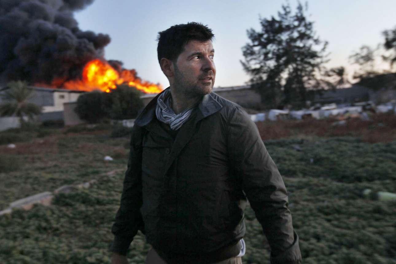 Ο ελληνοαμερικανός φωτογράφος, Κρις Χόντρος στέκεται μπροστά από ένα φλεγόμενο κτίριο στη Μισράτα της Λιβύης στις 18 Απριλίου του 2011. Ο διάσημος φωτογράφος έχασε την ζωή του δύο ημέρες αργότερα, στις 20 Απριλίου, από αντιαρματική ρουκέτα