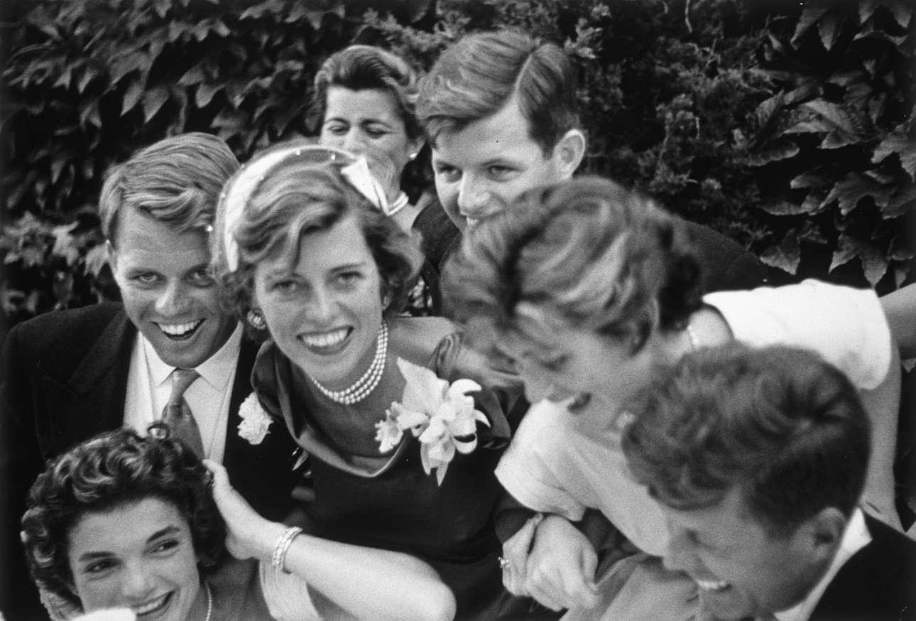 Το αμερικανικό Κάμελοτ στον γάμο της Τζάκι και του Τζον Κένεντι (διακρίνονται κάτω). Τον φακό κοιτάει με λαμπερό χαμόγελο ο Ρόμπερτ Κένεντι και η αδελφή του Τζιν Αν. Επάνω ο μικρότερος από τα εννέα αδέλφια, Τεντ Κένεντι
