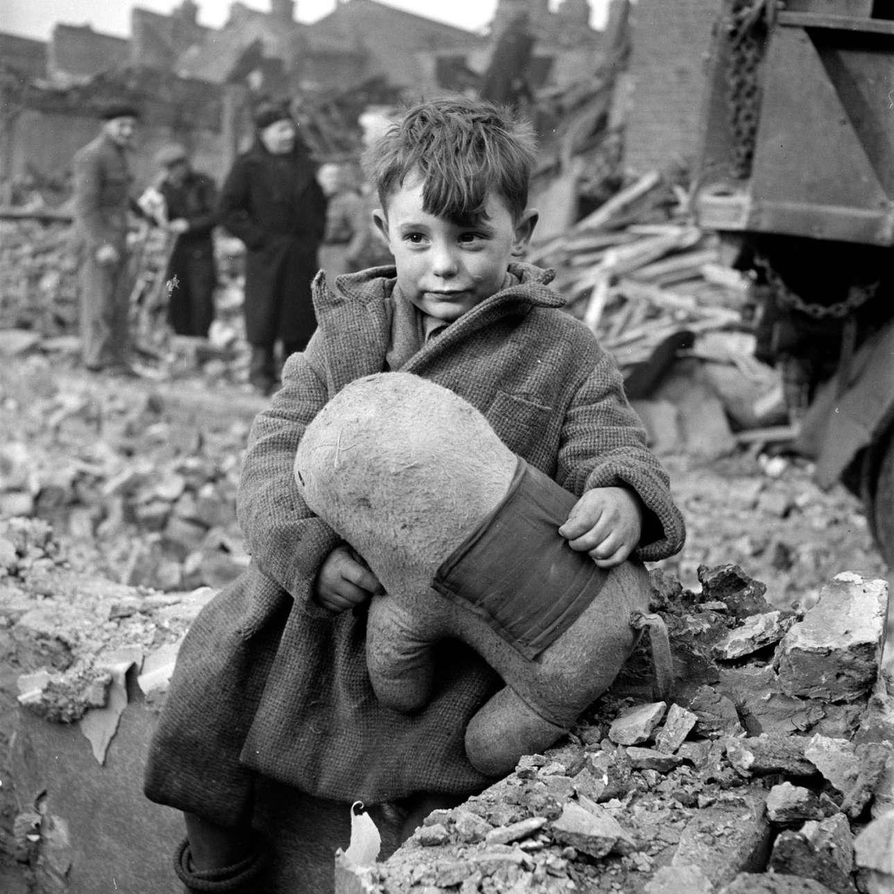 Εγκαταλειμμένο αγοράκι με ένα λούτρινο παιχνίδι αγκαλιά, ανάμεσα σε ερείπια, μετά από βομβαρδισμό του Λονδίνου από τους Ναζί, στον Β' Παγκόσμιο Πόλεμο