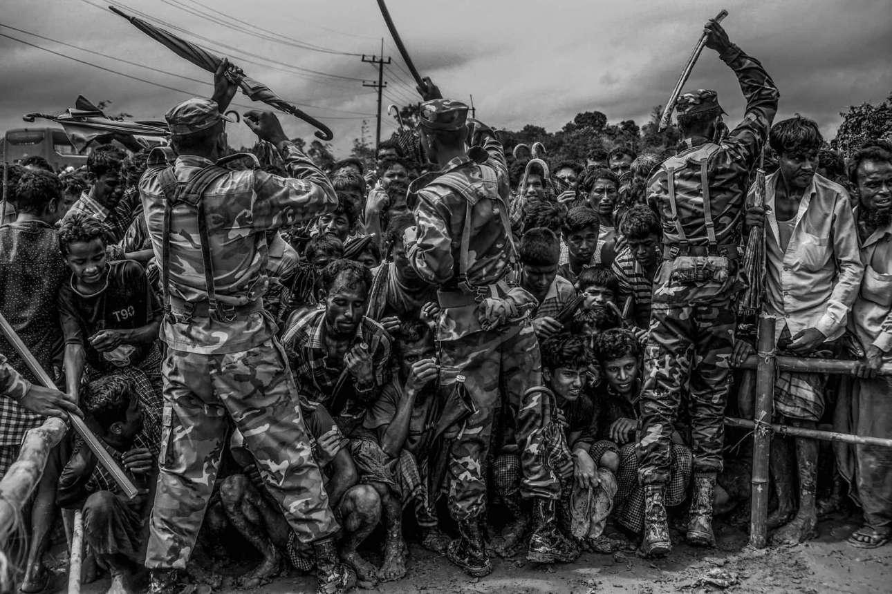 Πρώτη θέση, κατηγορία Επικαιρότητα και Ειδήσεις. Μπαγκλαντεσιανοί στρατιώτες επιχειρούν με βουρδουλιές να ελέγξουν το πλήθος: πρόσφυγες Ροχίνγκια περιμένουν να λάβουν επισιτιστική βοήθεια στον καταυλισμό Balukhali, στις 28 Σεπτεμβρίου του 2017