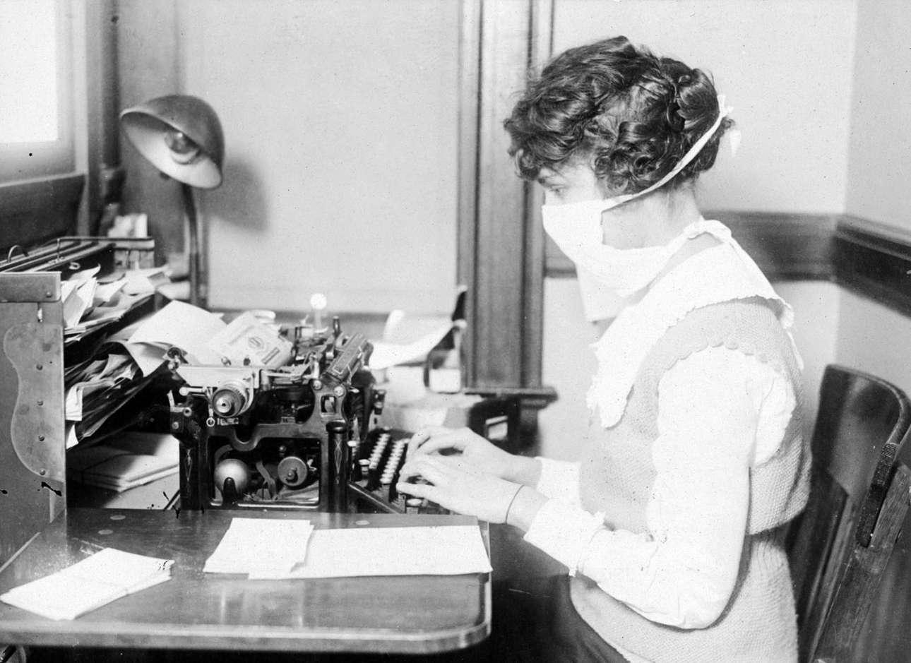 Δακτυλογράφος που φορά την ειδική μάσκα κατά της γρίπης εν ώρα εργασίας τον Οκτώβριο του 1918. Η ανησυχία για τη διάδοση της γρίπης στη Νέα Υόρκη, ανάγκασε όλους τους εργαζομένους να φορούν τις συγκεκριμένες μάσκες ενώ βρίσκονταν στη δουλειά τους