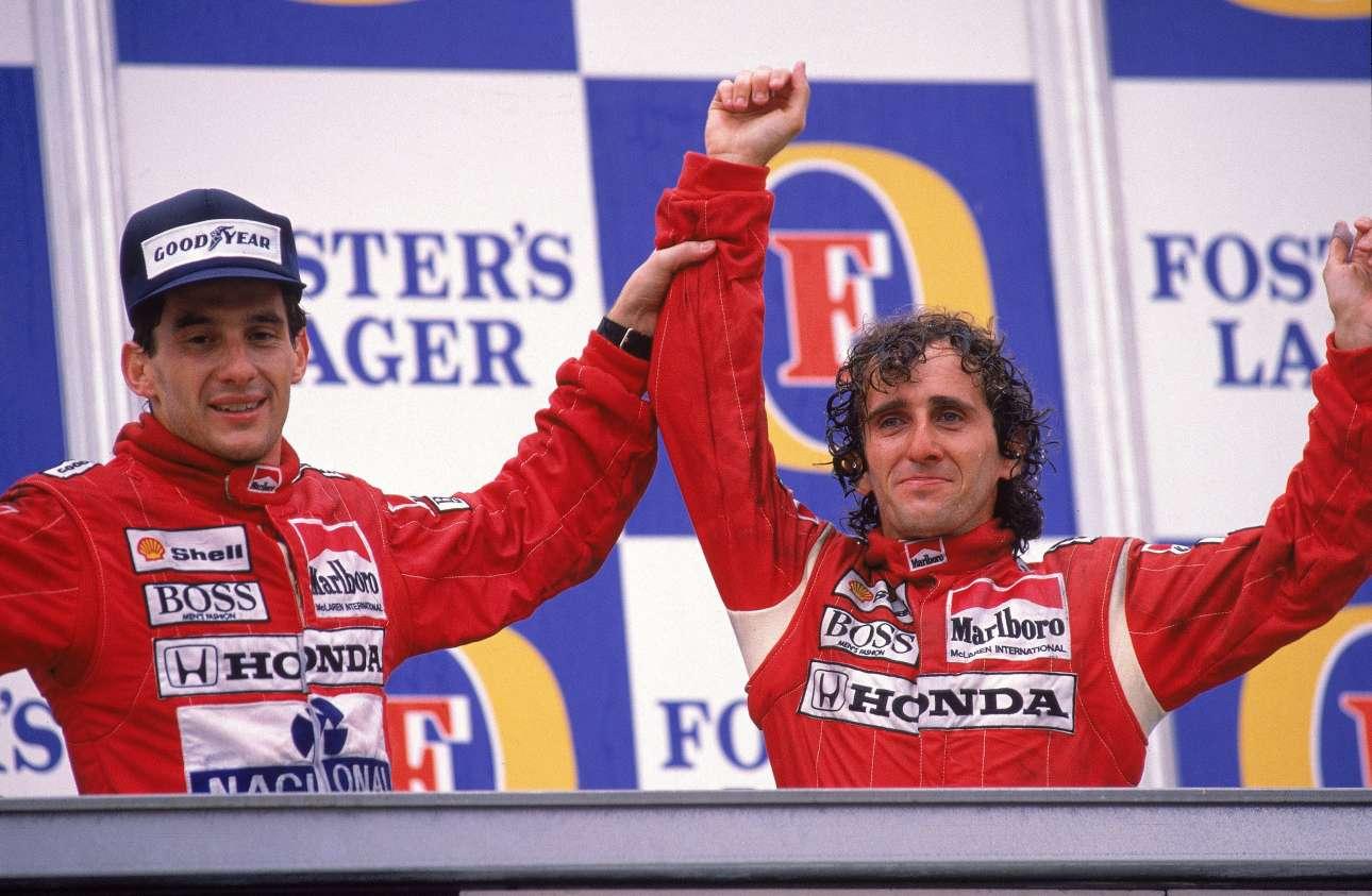 Νοέμβριος 1988. Ο Σένα πανηγυρίζει με τον Αλέν Προστ τη νίκη του δεύτερου στο γκραν πρι της Αδελαΐδας. Η δεύτερη θέση στον αγώνα έδωσε στον Βραζιλιάνο τον τίτλο του πρωταθλητή και γέννησε μια τρομακτική έχθρα στις πίστες μεταξύ των δύο ομόσταυλων πιλότων της McLaren-Honda