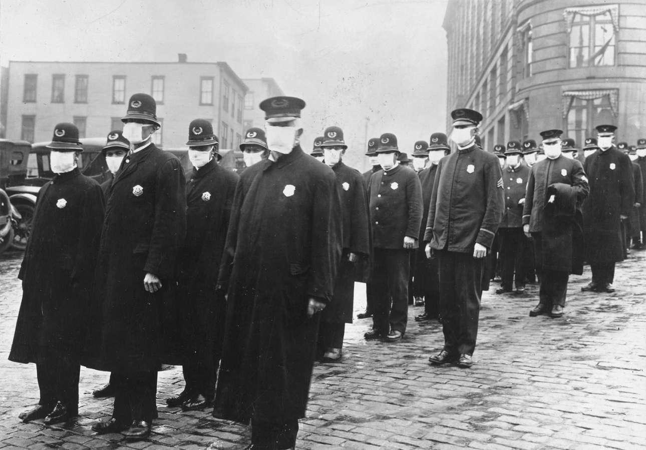 Αστυνομικοί στέκονται σε δρόμο του Σιάτλ, στην  Πολιτεία της Ουάσινγκτον, φορώντας προστατευτικές λευκές μάσκες που φτιάχτηκαν από τον Ερυθρό Σταυρό για προστασία από την πανδημία γρίπης