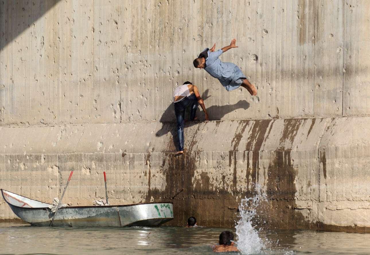 Πέμπτη, 24 Μαΐου, Συρία. Κόσμος βουτάει στα νερά του ποταμού Ευφράτη για να δροσιστεί κατά τη διάρκεια μιας δύσκολης ημέρας με υψηλές θερμοκρασίες στη Ράκκα