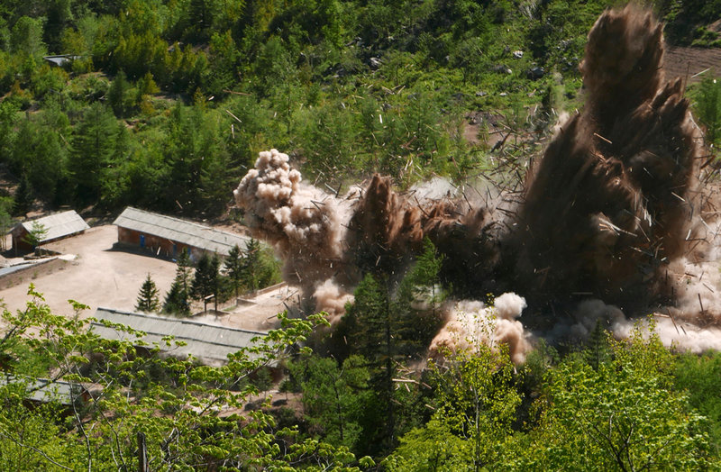 In this Thursday, May 24, 2018 photo, smoke and debris rise in the air as barracks buildings for guards and tunneling workers at North Korea's nuclear test site are blown up at Punggye-ri, North Hamgyong Province, North Korea. (APTN via AP)