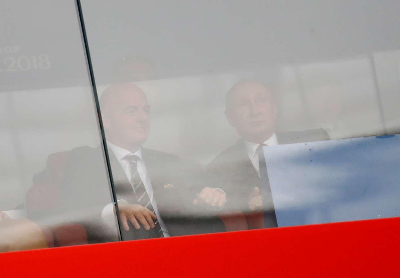 Ο ρώσος πρόεδρος Βλαντίμιρ Πούτιν και ο πρόεδρος της FIFA Τζάνι Ινφαντίνο, θολοί πίσω από το τζάμι -ωστόσο, στις θέσεις τους- περιμένουν το εναρκτήριο λάκτισμα