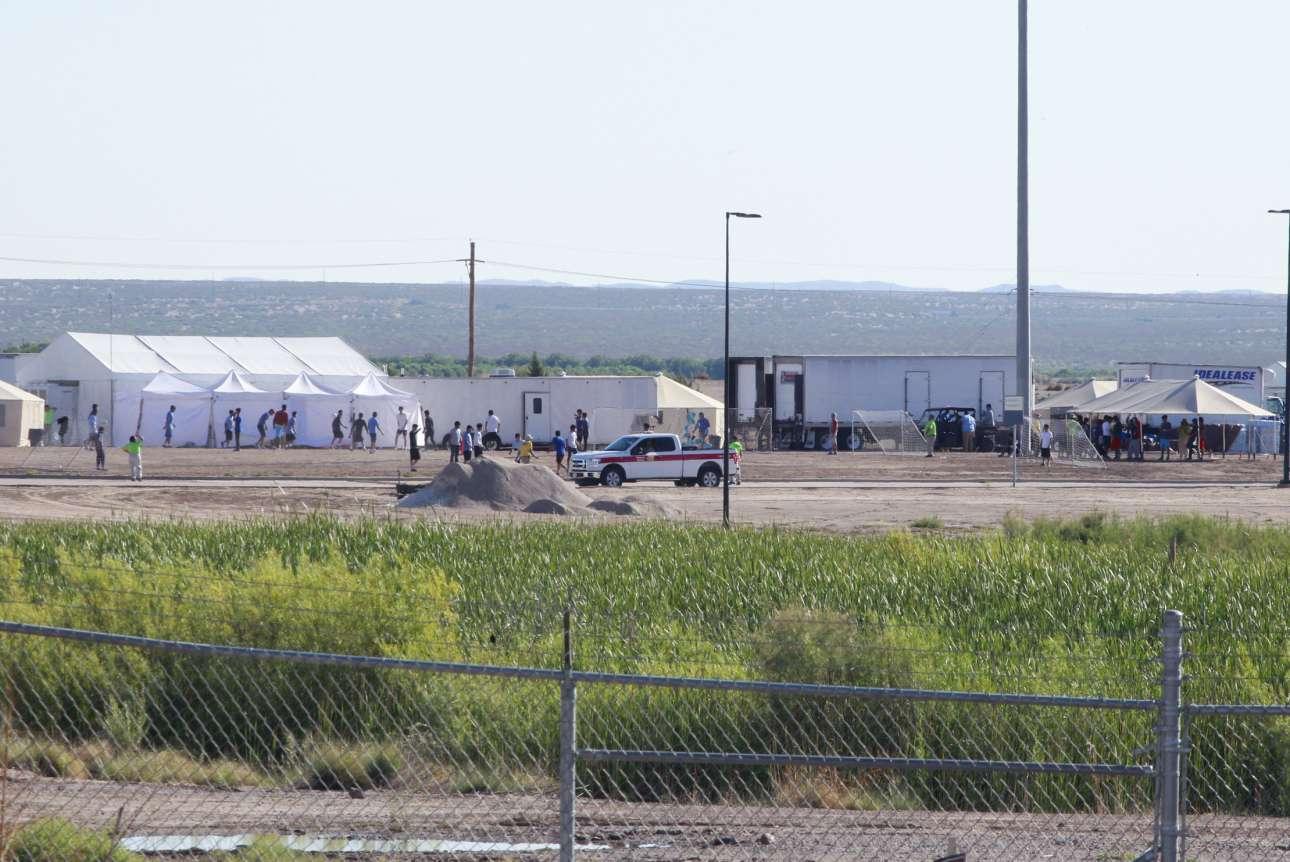 Μέσα από τον φράχτη διακρίνονται τα παιδιά των κρατούμενων μεταναστών να παίζουν ποδόσφαιρο