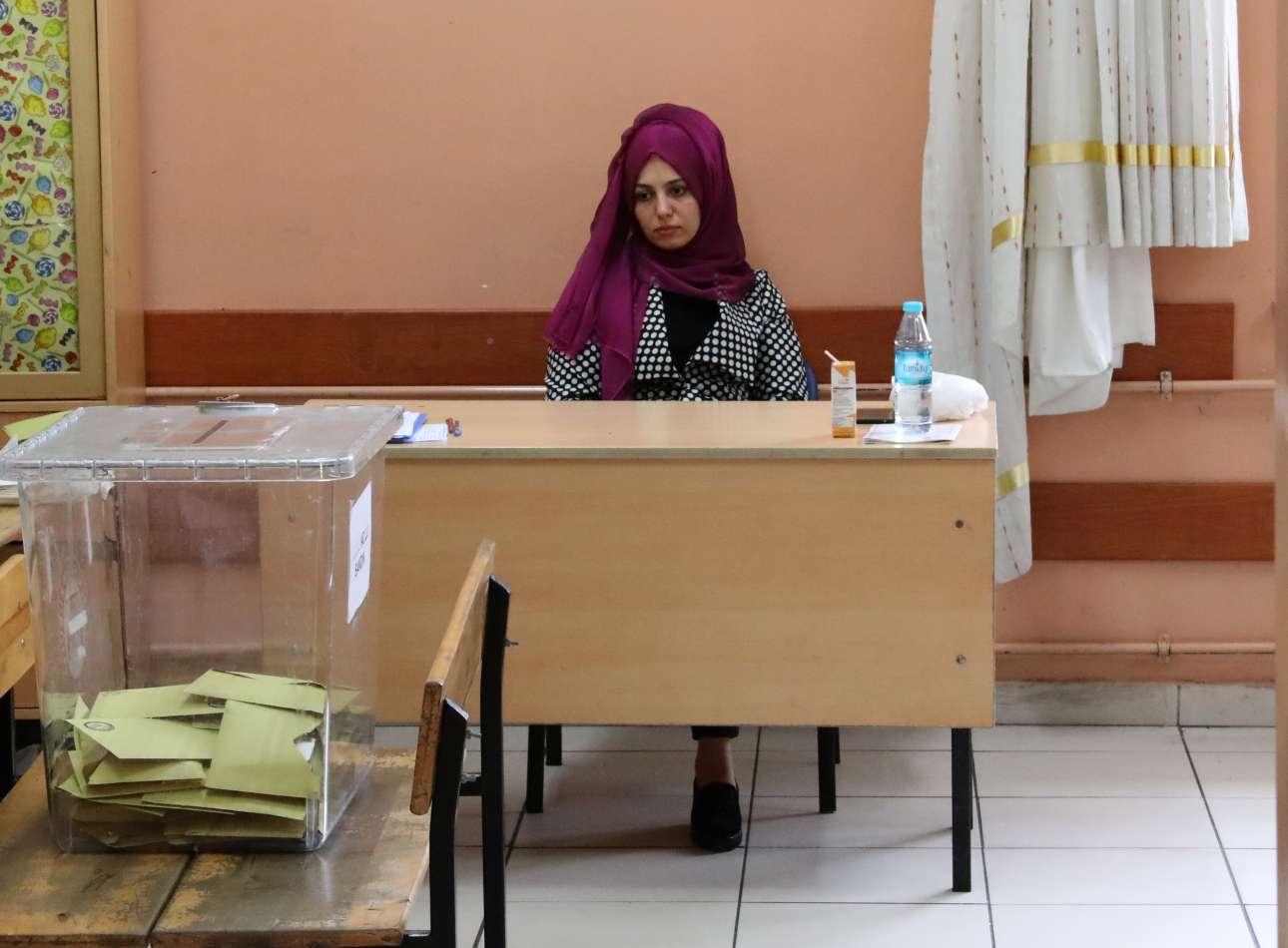 Η εκλογική αντιπρόσωπος περιμένει με ελαφρά απογοήτευση και κούραση τους ψηφοφόρους σε κέντρο στην Κωνσταντινούπολη