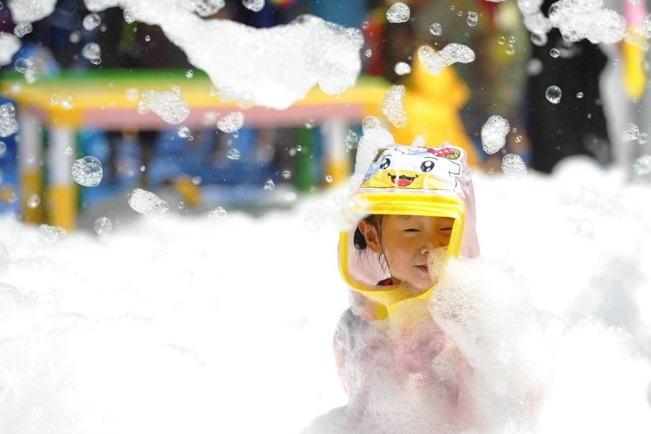 Δευτέρα, 25 Ιουνίου, Κίνα. Ενα μικρό κορίτσι διασκεδάζει σε πισίνα γεμάτη με αφρό στην πόλη Χουαϊάν