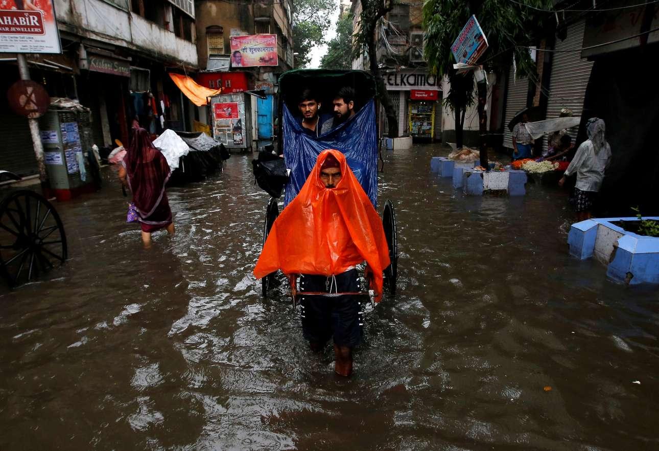 Τρίτη, 26 Ιουνίου, Ινδία. Στιγμιότυπο από τους δρόμους της Καλκούτας, κατά τη διάρκεια σφοδρής βροχόπτωσης