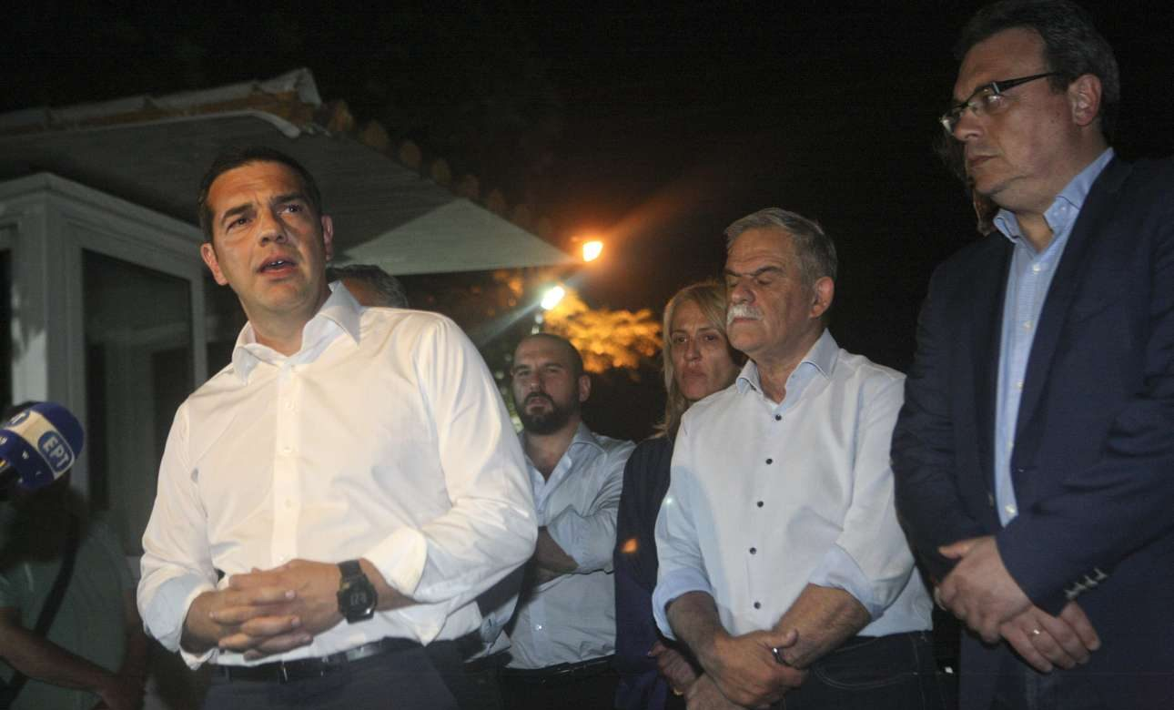 Ιούλιος 2018. Μετά την παρωδία της σύσκεψης στο Συντονιστικό, βγαίνει να κάνει δηλώσεις για την πυρκαγιά στην Ανατολική Αττική. Πίσω του η πένθιμη κομπανία: Τζανακόπουλος, Δούρου, Τόσκας, Φάμελος