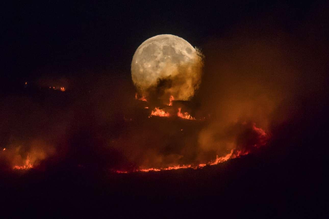 Τρίτη, 26 Ιουνίου, Βρετανία. To φεγγάρι «φλέγεται». Μία συγκλονιστική φωτογραφία από τη μεγάλη πυρκαγιά στο Στάλιμπριτζ, στην περιοχή του Μάντσεστερ