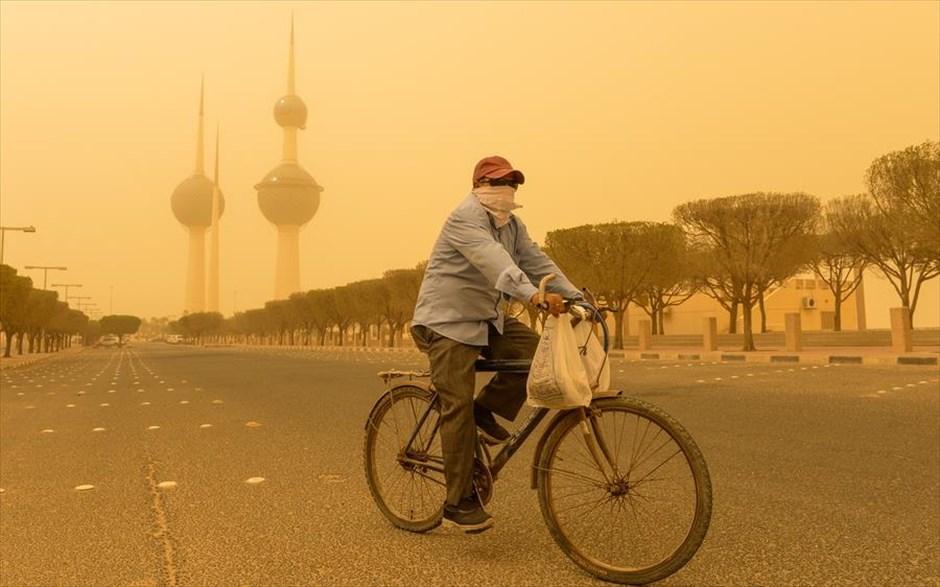 Πέμπτη, 28 Ιουνίου, Κουβέιτ. Ποδηλάτης διασχίζει την Πόλη του Κουβέιτ εν μέσω αμμοθύελλας