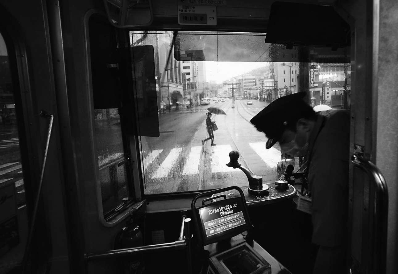 «Μία ακόμα βροχερή μέρα στο Ναγκασάκι, Κιούσου». Πρώτη θέση στην κατηγορία Πόλεις. Η θέα του κεντρικού δρόμου στο Ναγκασάκι μέσα από το τραμ, μία βροχερή μέρα. Το τραμ είναι βίντατζ αλλά έχει εξοπλιστεί με σύγχρονο μηχάνημα έκδοσης εισιτηρίων. Εισπράκτορας δεν υπάρχει πια, μόνο ο μοναχικός οδηγός.  Το ήσυχο τοπίο σε αντίθεση με τα πολύβουα κέντρα του Τόκιο και της Οσάκα τράβηξε την προσοχή του φωτογράφου, ο οποίος βρήκε τη βόλτα με το βίνταζ τραμ μέσα στην ιστορική πόλη Ναγκασάκι «μία αξιομνημόνευτη εμπειρία»