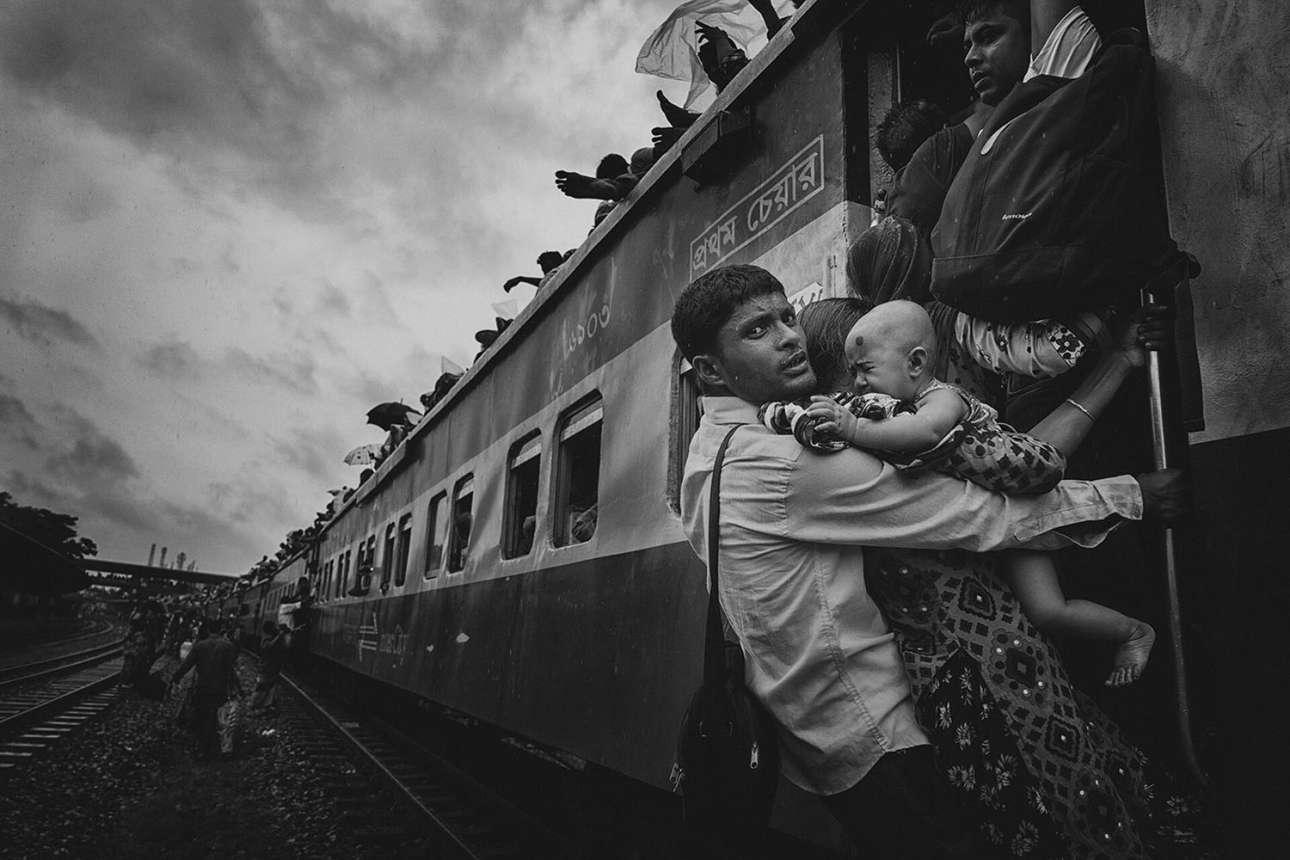 «Ταξίδι με προκλήσεις». Τρίτη θέση στην κατηγορία Ανθρωποι. Ενας άνδρας με την οικογένειά του προσπαθεί να στριμωχτεί μέσα στο τρένο που αναχωρεί από τον σταθμό της Ντάκας στο Μπαγκλαντές, για να περάσει τη γιορτή του Εΐντ κοντά σε αγαπημένους στο χωριό του