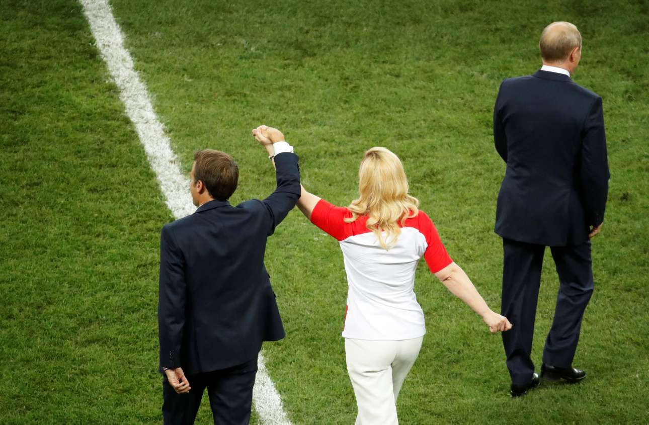 Ποδοσφαιρικός και πολιτικός πολιτισμός. Εμανουέλ Μακρόν και Κολίντα Γκράμπαρ-Κιτάροβιτς εισέρχονται πιασμένοι χέρι-χέρι στον αγωνιστικό χώρο για την τελετή απονομής του Παγκοσμίου Κυπέλλου