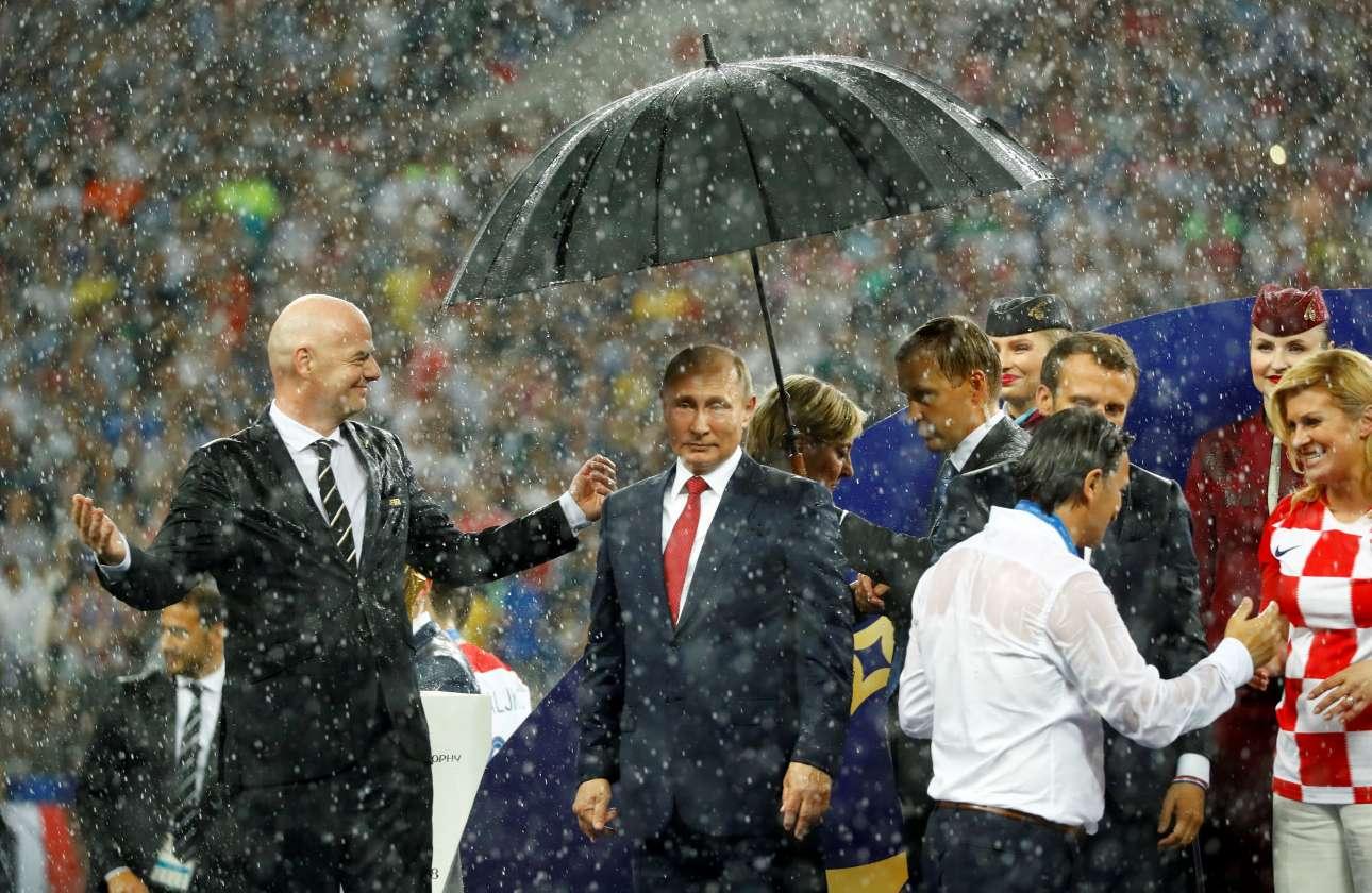 Ωραίος οικοδεσπότης... Οι ουρανοί άνοιξαν πάνω από το «Λουζνίκι» αλλά ομπρέλα προσέφεραν μόνο στον ρώσο πρόεδρο Βλαντίμιρ Πούτιν. Οι υπόλοιποι πέρασαν τη μεγαλύτερη διάρκεια της τελετής απονομής μεταλλείων υπό καταρρακτώδη βροχή