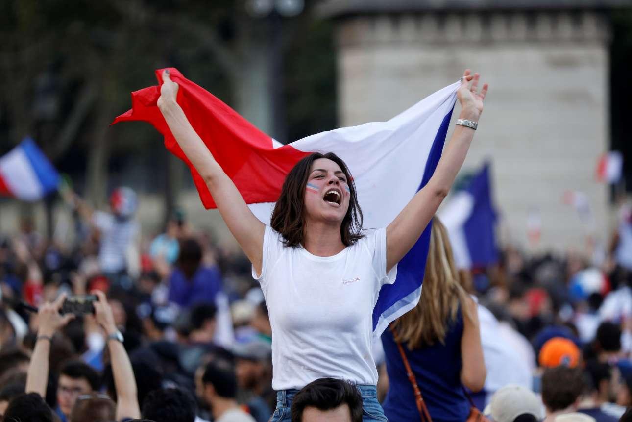 Νεαρή Γαλλίδα στους ώμους του φίλου της πανηγυρίζει με τη γαλλική σημαία στα Ηλύσια Πεδία