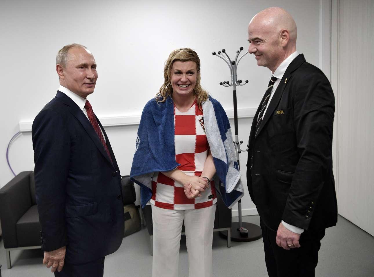 Μετά την ψυχρολουσία. Η Κολίντα Γκράμπαρ-Κιτάροβιτς με μια πετσέτα προσπαθεί να συνέλθει από τη νεροποντή, ανάμεσα στον Βλαντίμιρ Πούτιν και τον επικεφαλής της FIFA Τζιάνι Ιφαντίνο