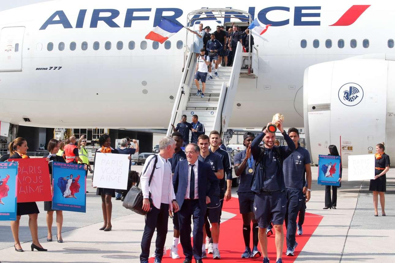 Παίκτες και τεχνικό επιτελείο αποβιβάζονται. Αεροσυνοδοί κρατούν κάρτες με το σύνθημα: «Το Παρίσι σας αγαπά»
