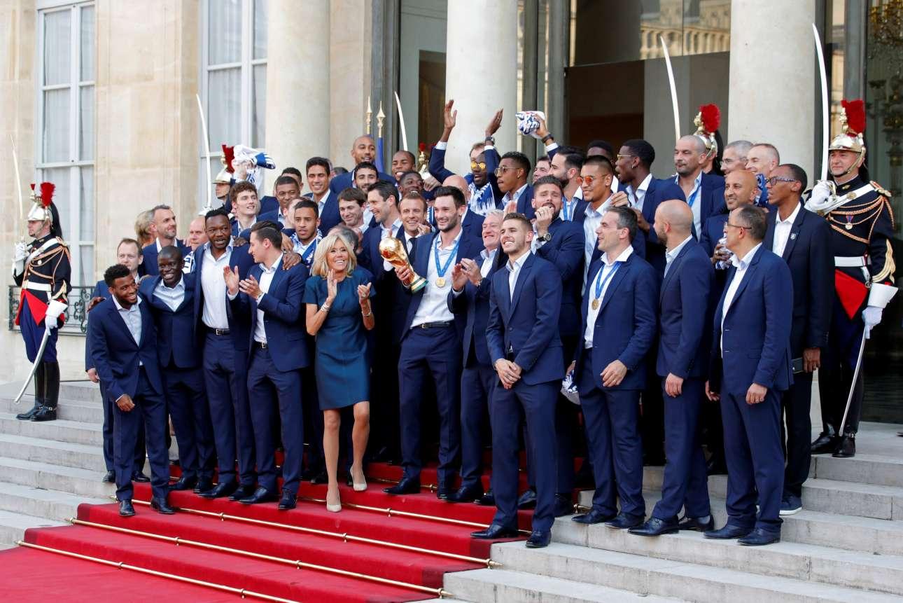 Η Μπριζίτ Μακρόν χειροκροτεί τους παγκόσμιους πρωταθλητές στο Μέγαρο των Ηλυσίων. Ο σύζυγός της, πρόεδρος της Γαλλικής Δημοκρατίας, Εμανουέλ Μακρόν διακρίνεται αριστερά του Ούγκο Λιορίς που κρατά το Παγκόσμιο Κύπελλο
