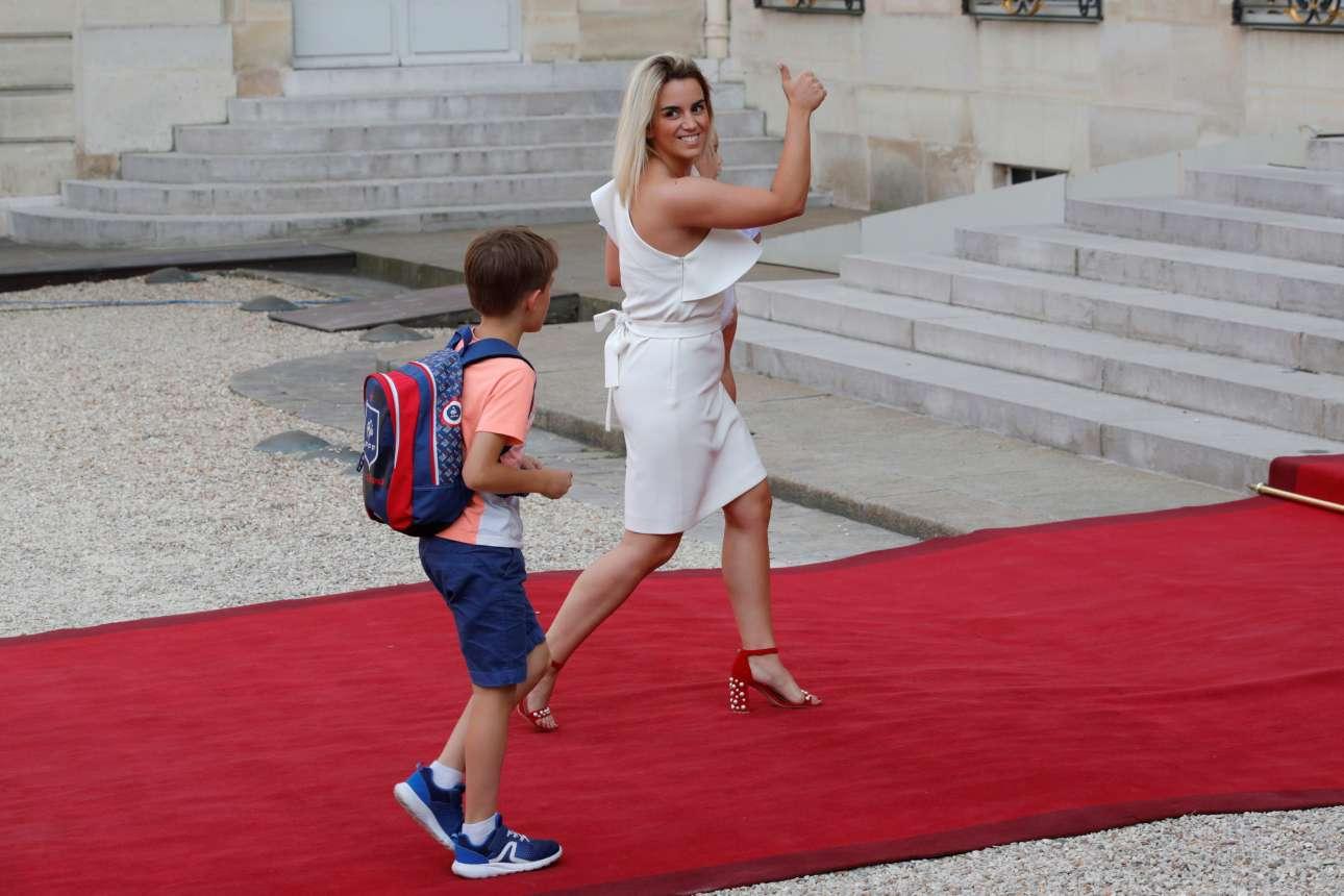 Η Ερικα Τσοπερένα, σύζυγος του Αντουάν Γκριζμάν, καταφθάνει με τον γιο τους στο Μέγαρο των Ηλυσίων για την τελετή προς τιμήν των παγκόσμιων πρωταθλητών
