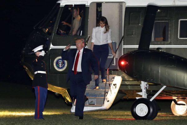 Ο Ντόναλντ Τραμπ ακολουθούμενος από τη Μελάνια, αποβιβάζεται υπό βροχή από το ελικόπτερο που τον μετέφερε στον Λευκό Οίκο φωτό: REUTERS/ Kevin Lamarque)