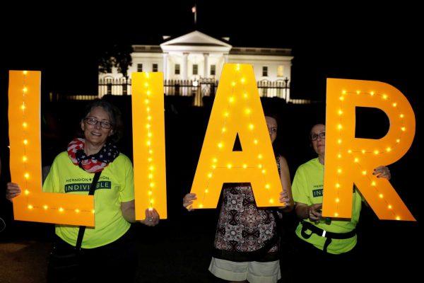 Διαμαρτυρόμενοι έξω από τον Λευκό Οίκο με... φωτεινές επιγραφές που γράφουν «Liar» Ψεύτη») φωτό: REUTERS/Kevin Lamarque)
