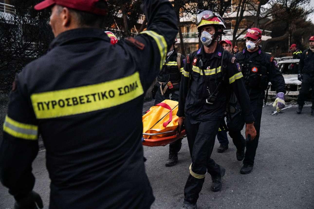 Ανδρες της πυροσβεστικής μεταφέρουν νεκρούς που έχασαν τη μάχη με τις φλόγες