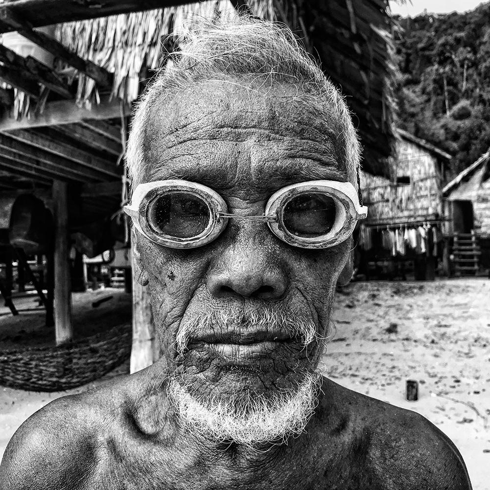 Πρώτη θέση στην κατηγορία Πορτρέτο. Ο Μόκεν, το μεγαλύτερο μέλος της κοινότητας περίπου 300 θαλάσσιων τσιγγάνων του μικροσκοπικού νησιού Phang Nga στην Ταϊλάνδη, ποζάρει στην παραλία φορώντας χειροποίητα ξύλινα γυαλιά κολύμβησης