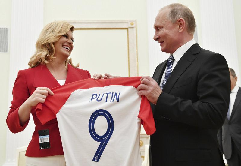 Croatian President Kolinda Grabar Kitarovic, left, presents a T-shirt to Russian President Vladimir Putin during their meeting in the Kremlin in Moscow, Russia, Sunday, July 15, 2018. (Yuri Kadobnov/Pool Photo via AP)