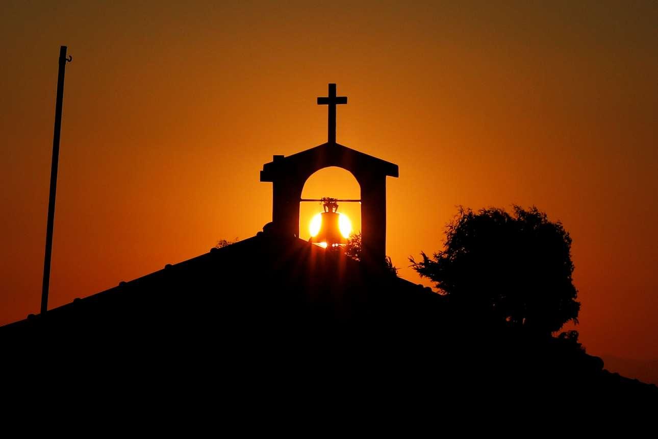 Ο ήλιος δύει πίσω από μία καμπάνα των αδελφών Γαλανόπουλων, στα Σύβοτα. Η μεγαλύτερη καμπάνα που έχουν κατασκευάσει ο Χρήστος και ο Θωμάς ζυγίζει 3,5 τόνους και βρίσκεται σε μία εκκλησία της βόρειας Ελλάδας. Δυστυχώς όμως πια υπάρχει ελάχιστη ζήτηση εδώ και οι εξαγωγές είναι αυτές που κρατούν την επιχείρηση ζωντανή
