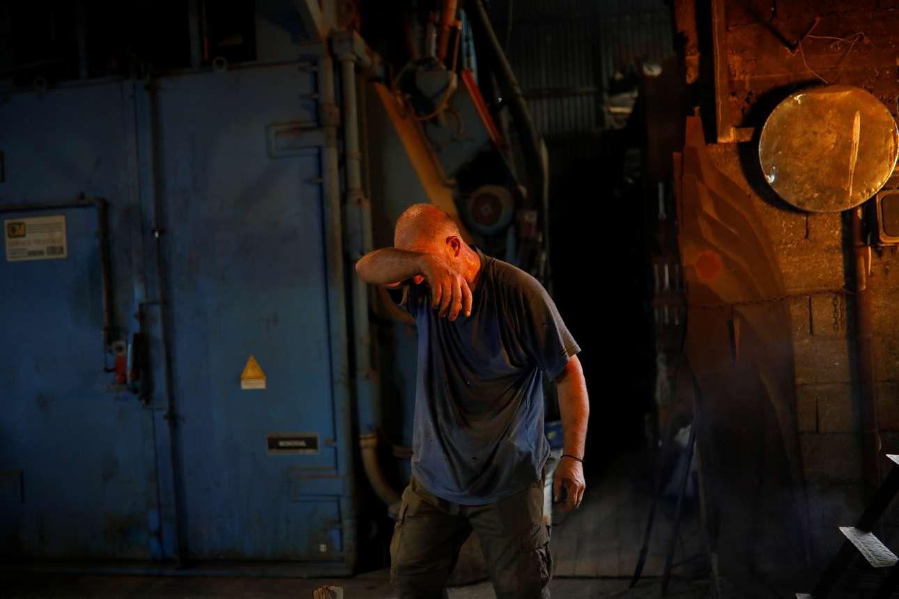 Υπάλληλος στο χυτήριο σκουπίζει τον ιδρώτα του, δίπλα από τον φλεγόμενο κλίβανο. Εξαιτίας της κρίσης, οι αδελφοί Γαλανόπουλοι έπρεπε να μειώσουν το προσωπικό από τα 9 άτομα στα έξι