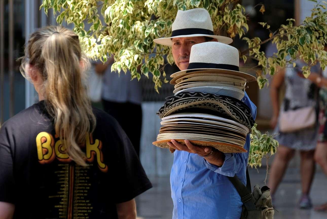 Ανδρας πουλά καπέλα σε τουρίστες κατά τη διάρκεια ενός αποπνικτικού μεσημεριού στο κέντρο της Βαλένθια στην Ισπανία