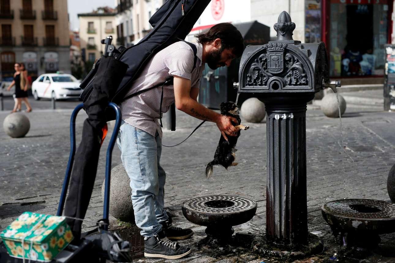 Ανδρας ρίχνει λίγο νερό στο μικρό σκυλί του προκειμένου να το προστατέψει από τις εξαιρετικά υψηλές θερμοκρασίες στην Μαδρίτη της Ισπανίας