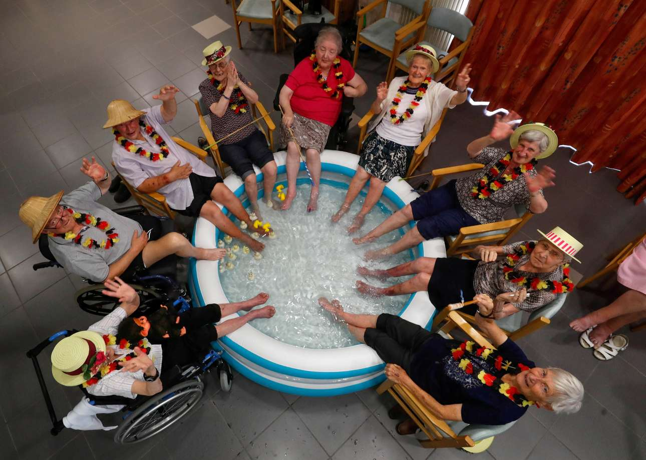Ηλικιωμένοι και ηλικιωμένες απολαμβάνουν την δροσιά μίας μικρής πλαστικής πισίνας σε οίκο ευγηρίας του Βελγίου