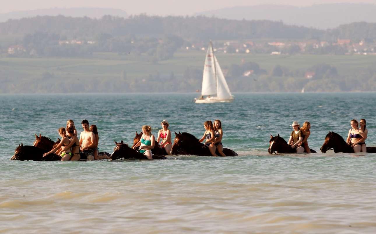 Ανθρωποι και άλογα δροσίζονται στη Λίμνη Κωνσταντίας μία ζεστή ημέρα στην Ελβετία