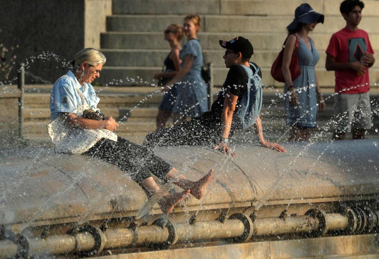 Μία γυναίκα δροσίζει τα πόδια της σε συντριβάνι στο κέντρο της Βιέννης στην Αυστρία