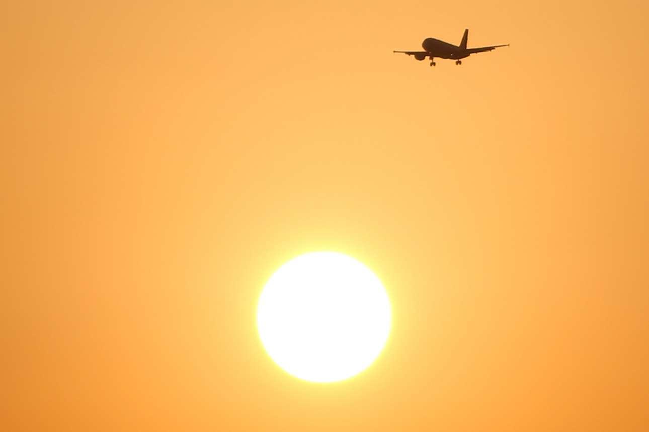 Επιβατικό αεροσκάφος φαίνεται να πετά πάνω τον Ηλιο που δύει στην Μάλαγα της Ισπανίας