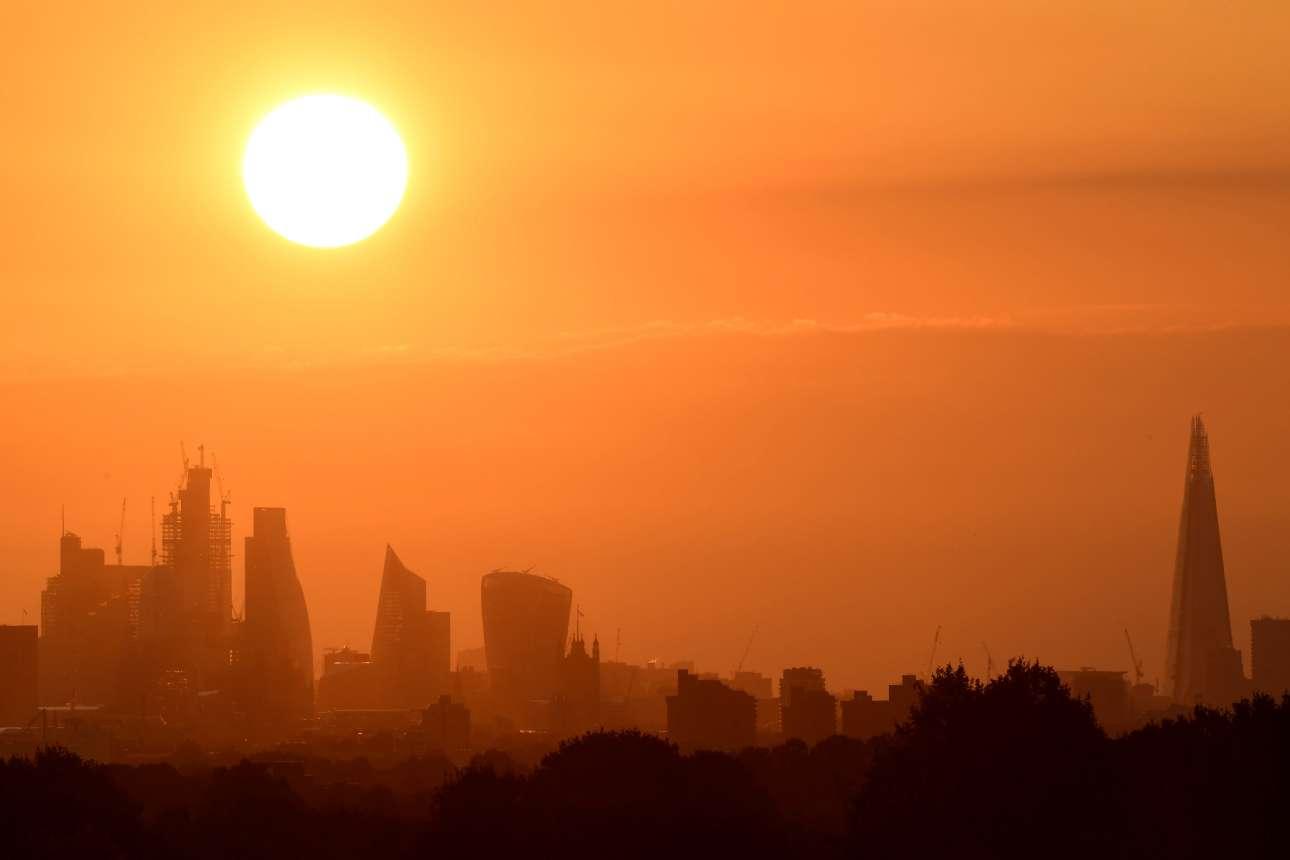 Ο Ηλιος υψώνεται πάνω από τους ουρανοξύστες του Λονδίνου. Ακόμα και η βροχερή Βρετανία αντιμετωπίζει αυτές τις ημέρες ένα σπάνιο κύμα καύσωνα