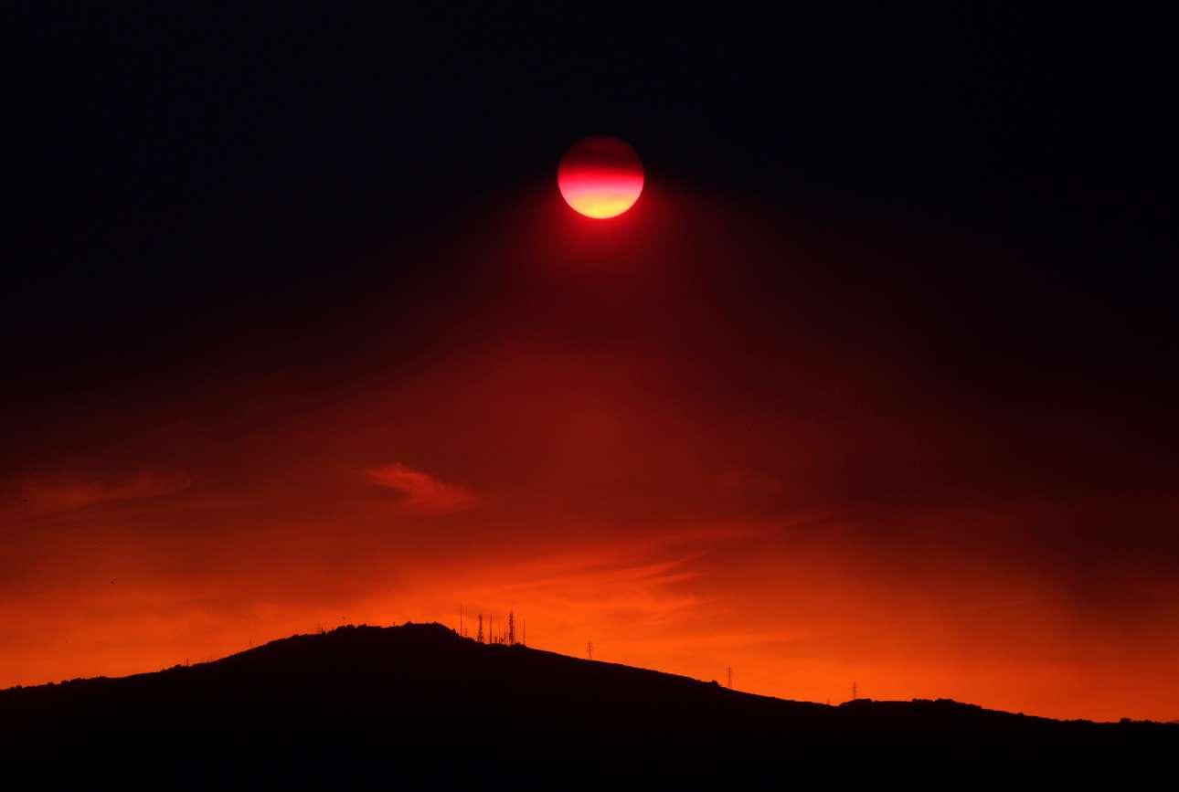 Ο μεσημβρινός ήλιος της Κυριακής απέκτησε ένα εφιαλτικό χρώμα καθώς οι καπνοί από τη μεγάλη πυρκαγιά της Εύβοιας κάλυψαν τον αττικό ουρανό