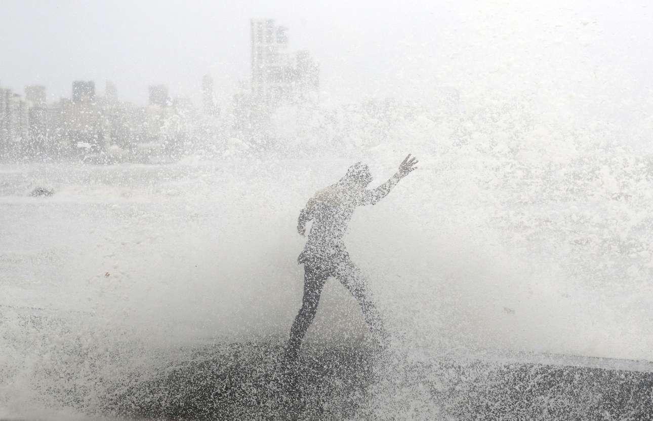 13 Αυγούστου. Ανδρας χάνει την ισορροπία του παλεύοντας με ένα πελώριο κύμα σε παραλία του Μουμπάι, στην Ινδία