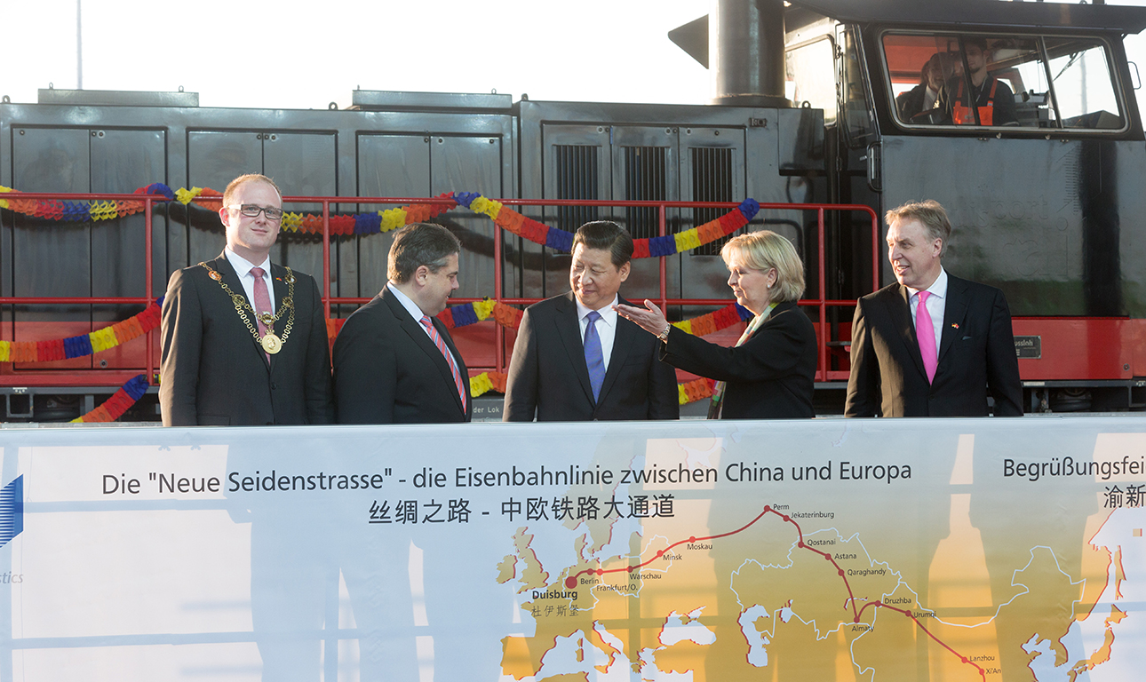 """DUISBURG, GERMANY - MARCH 29: (L-R) Lord Mayor of the city of Duisburg Soren Link (SDP), Vice Chancellor and Economy and Energy Minister Sigmar Gabriel (SPD), Chinese President Xi Jinping, Prime Minister of the German State of Northrhine-Westfalia Hannelore Kraft and CEO of Duisburger Hafen AG (Duisport) Erich Staake attend the arrival of """"Yuxinou"""" container train at the Logport terminal on March 29, 2014 in Duisburg, North Rhine-Westphalia, Germany. The train, which is up to 750 meters long, links the Duisburg shipping port directly with the Chinese city of Chongqing, located 10,000 kilometers away. Xi Jinping is on a two-day official visit to Germany. (Photo by Pool/Getty Images)"""