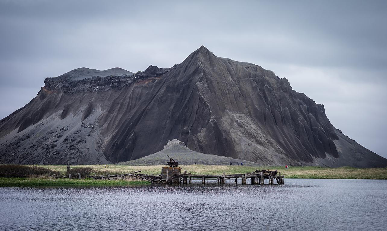 Κουρίλες νήσοι: ένας σάπιος ντόκος στο νησί Ατλασόβα, μπροστά από έναν ηφαιστειογενή λόφο