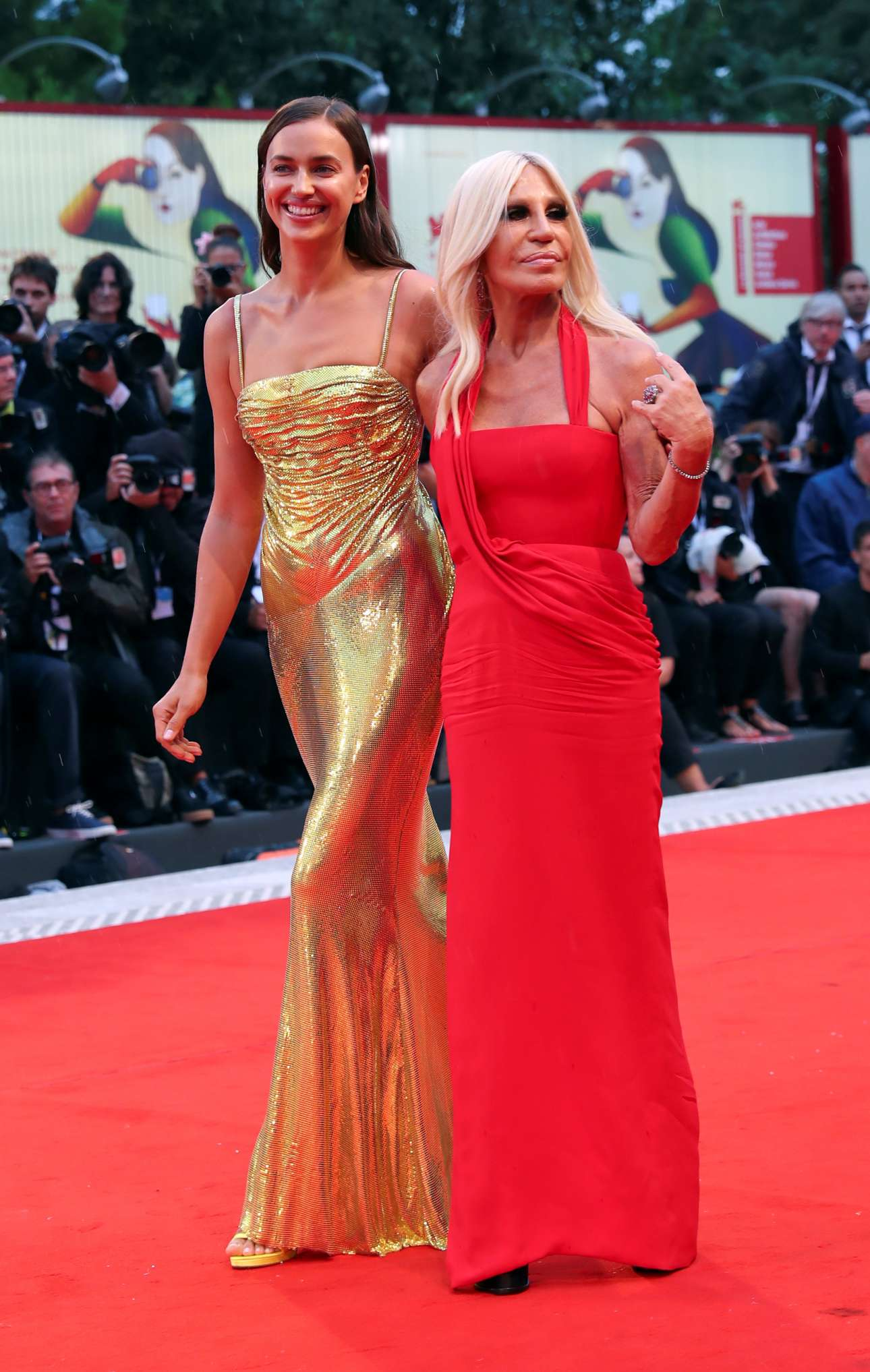 Η πανέμορφη Ιρίνα Σάικ με χρυσή λαμπερή τουαλέτα Versace, πηγαίνει αγκαλιά με τη σχεδιάστρια Ντονατέλα Βερσάτσε να παρακολουθήσει την πρεμιέρα της ταινίας «Ενα αστέρι γεννιέται»