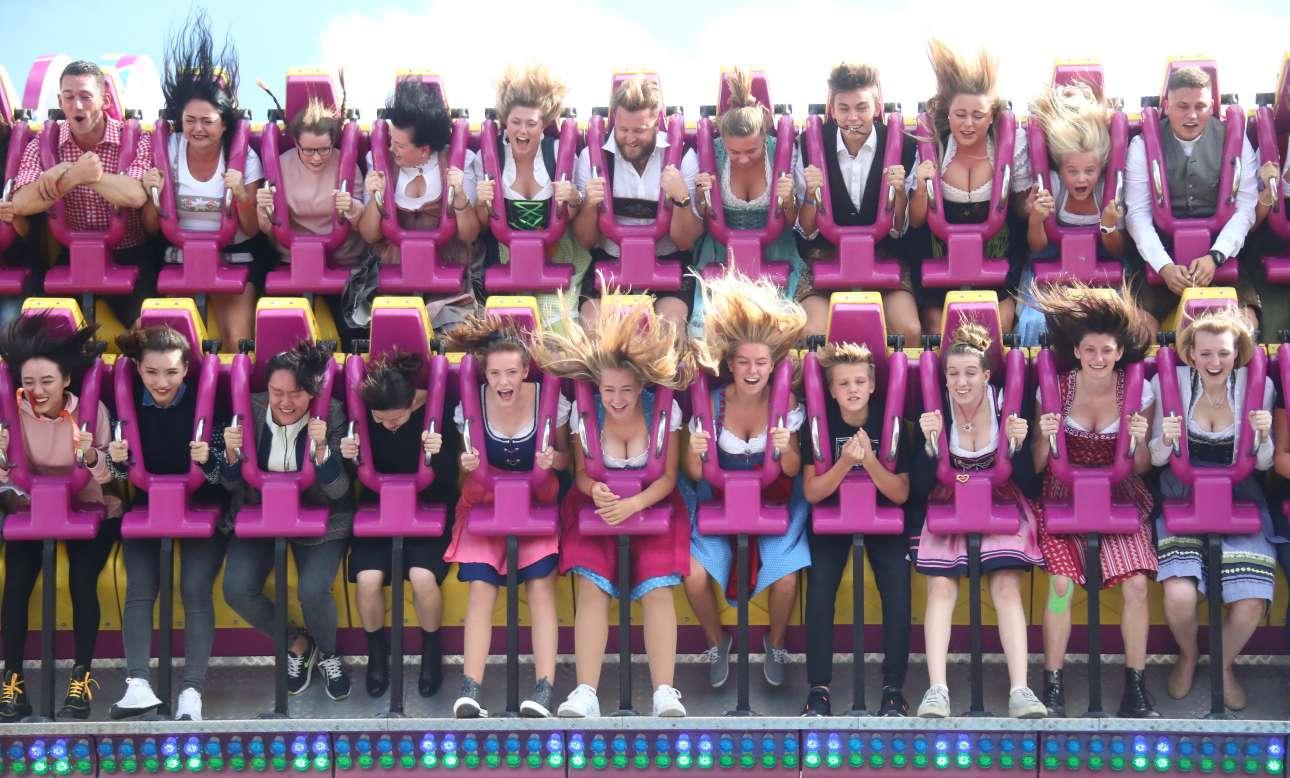 Βαυαρικές φορεσιές και πλατιά χαμόγελα στον αέρα, σε παιχνίδια του λούνα παρκ που βρίσκονται στο χώρο του Φεστιβάλ