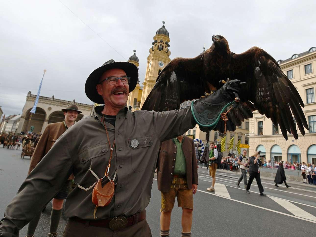 Κρατώντας έναν αετό στο χέρι, άνδρας συμμετέχει στην παρέλαση του Οκτόμπερφεστ στο Μόναχο