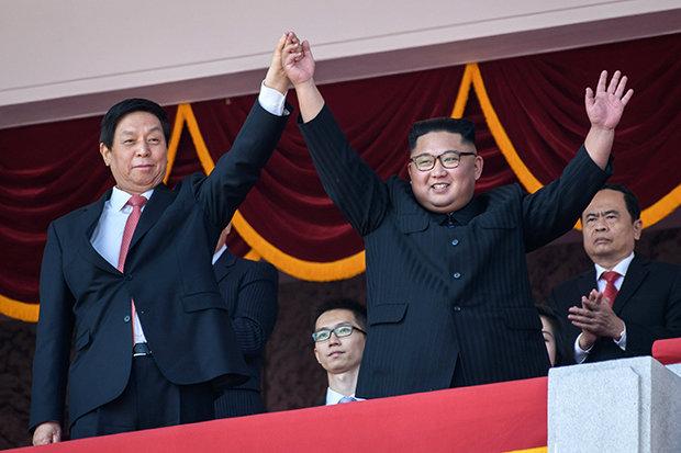 Μαζί με τον Κιμ Γιονγκ Ουν στο βήμα, χαιρετούσε το πλήθος ο Κινέζος Λι Ζιανσού, ένα από τα επτά μέλη της μόνιμης επιτροπής του πολιτικού γραφείου του Κομμουνιστικού Κόμματος της Κίνας, και τρίτος πιο υψηλόβαθμος στην ιεραρχία του